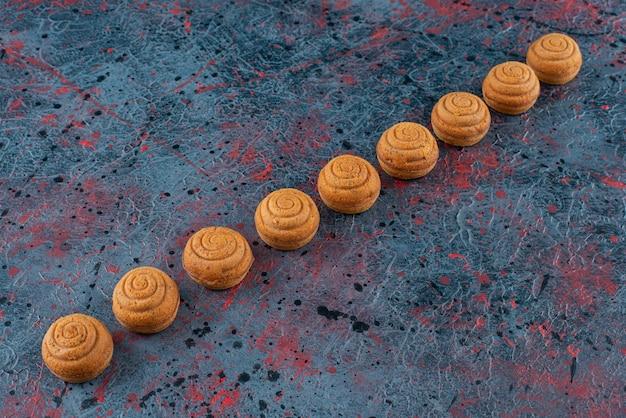Conjunto de doces deliciosos biscoitos redondos frescos em um fundo escuro.
