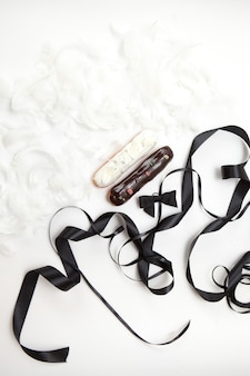 Conjunto de dois eclairs com uma decoração de chocolate preto e branco decorado com penas brancas e fitas marrons