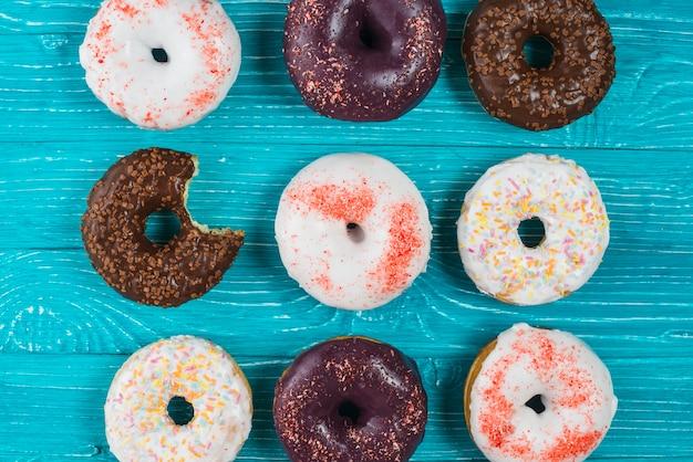 Conjunto de donuts mordidos frescos com cobertura de chocolate e polvilha