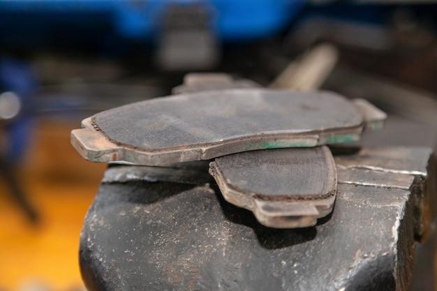Conjunto de duas velhas pastilhas de freio de automóvel em uma garagem.