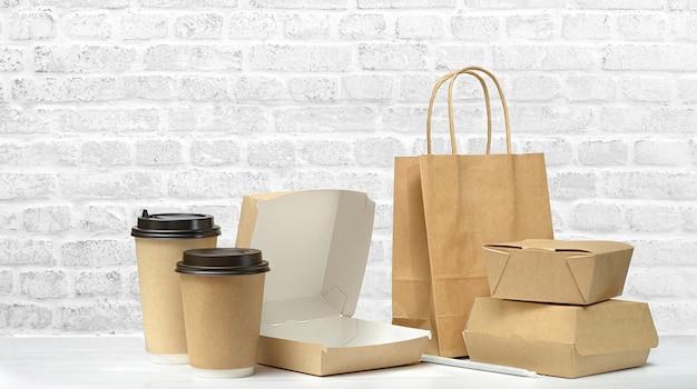 Conjunto de embalagens de fast food. caixa de comida aberta vazia, xícaras de café de papel, saco de papel marrom na mesa no fundo da parede de tijolo