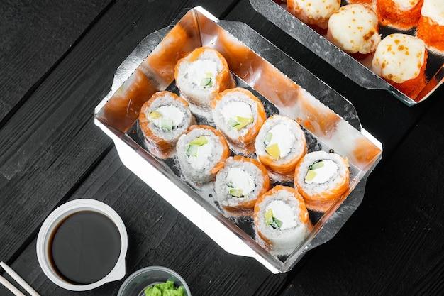Conjunto de entrega de sushi roll, em mesa de madeira preta