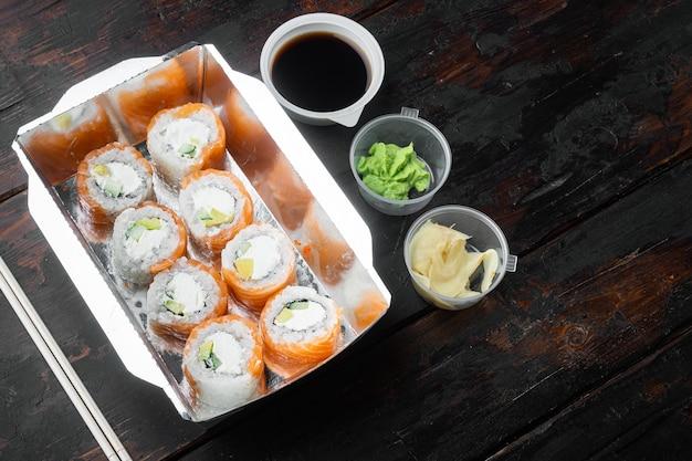 Conjunto de entrega de sushi roll, em velha mesa de madeira escura