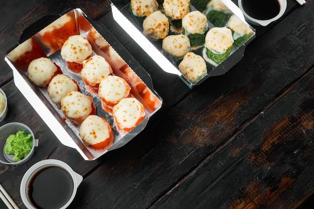 Conjunto de entrega de sushi roll, no fundo da velha mesa de madeira escura, com copyspace e espaço para texto