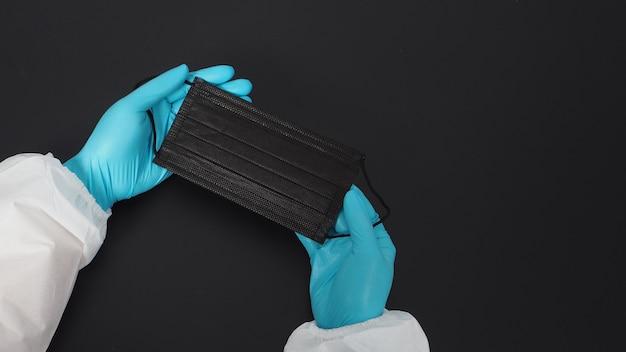 Conjunto de epi e luvas de uso de duas mãos e máscara facial preta. coloque um fundo preto.