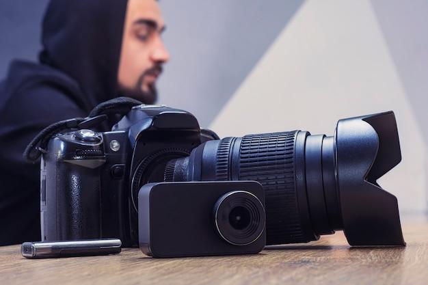 Conjunto de equipamentos para fotografia e filmagem de vídeo. uma câmera com uma lente, uma câmera de ação e uma unidade flash usb em uma mesa de madeira contra o fundo de um fotógrafo.