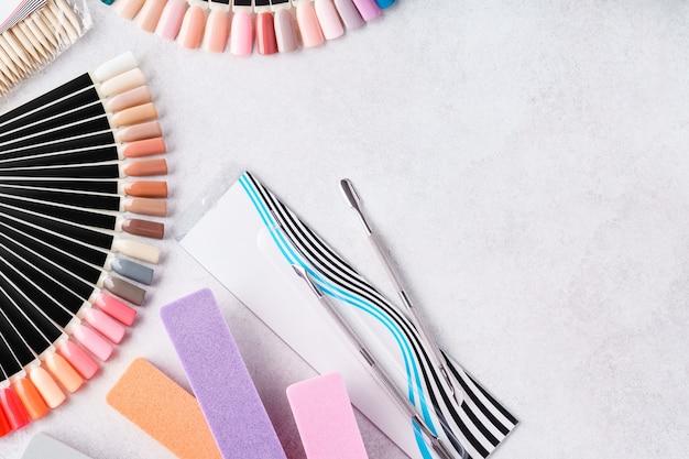 Conjunto de equipamentos profissionais de manicure - lixas de unhas, paletas de amostras, ferramentas. postura plana.