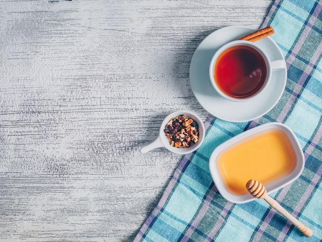 Conjunto de ervas de mel e chá e uma xícara de chá em um pano de piquenique e fundo cinza de madeira. vista do topo. espaço para texto