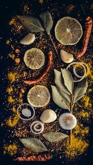Conjunto de especiarias: cebola, limão, alho, pimenta vermelha, pimentão, pimenta preta, sementes de cominho, cominho, curry, louros, açafrão, curcuma.