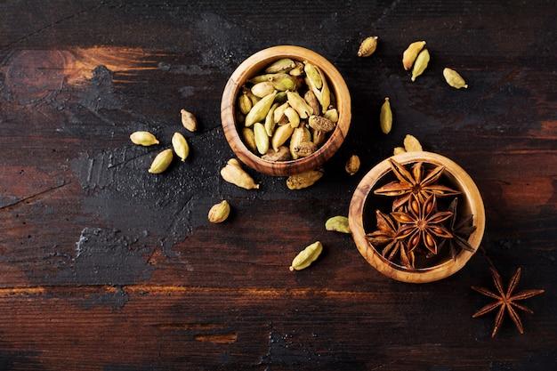 Conjunto de especiarias de anis estrelado, cardamomo, canela e açúcar mascavo em fundo de madeira velho. postura plana.