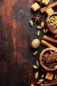 Conjunto de especiarias de anis estrelado, cardamomo, canela e açúcar mascavo em uma superfície de madeira velha
