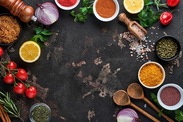 Conjunto de especiarias e ervas aromáticas indianas em um fundo de pedra preta. cúrcuma, endro, páprica, canela, açafrão, manjericão e alecrim em uma colher. vista do topo. brincar.