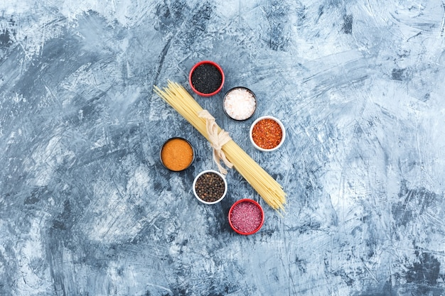 Conjunto de especiarias e espaguete em um fundo de gesso cinza. vista do topo.