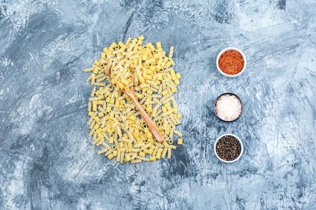 Conjunto de especiarias e massas espalhadas em uma colher de pau em um fundo de gesso sujo. colocação plana.