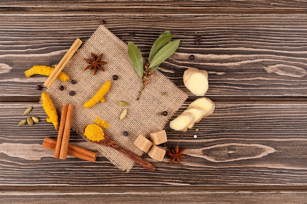Conjunto de especiarias picantes para fazer bebidas indianas: chá masala, leite dourado e outros. mesa de madeira.