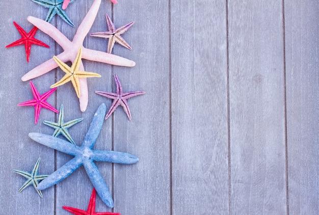 Conjunto de estrelas do mar multicoloridas em uma placa de madeira como uma borda com espaço de cópia