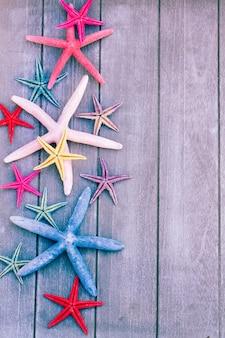 Conjunto de estrelas do mar multicoloridas em uma placa de madeira como uma borda