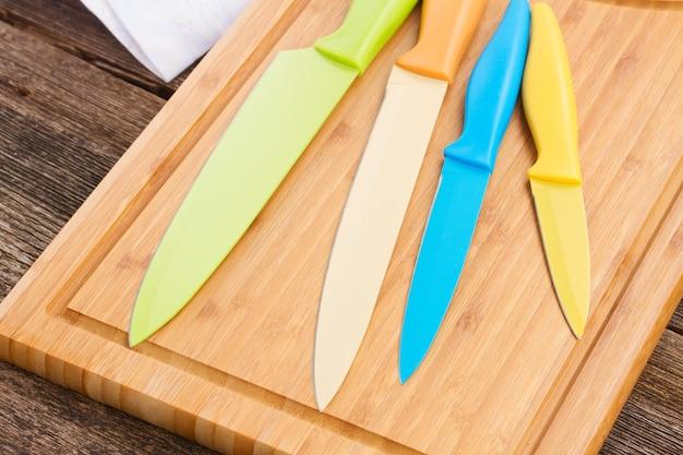 Conjunto de facas de cerâmica coloridas na tábua de madeira