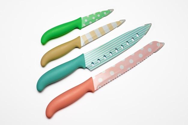 Conjunto de facas de cozinha coloridas de aço inoxidável ou cerâmica pintadas, isolado no fundo branco.