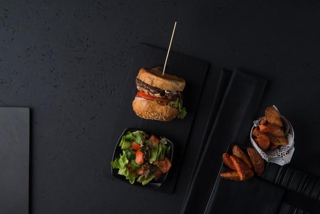 Conjunto de fast food, cheeseburger com salada e batatas em um fundo preto, vista superior