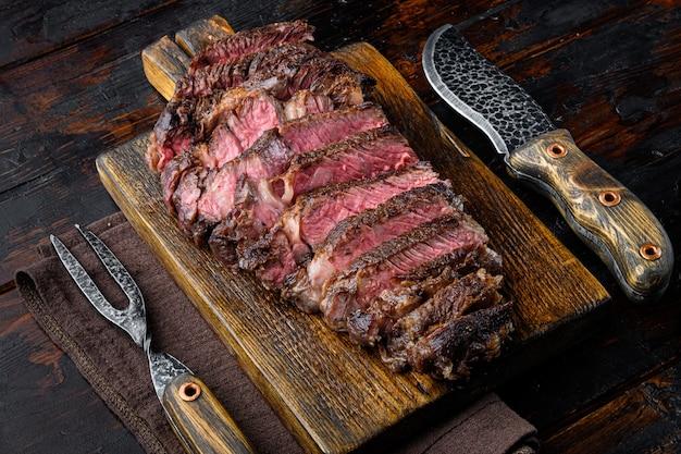 Conjunto de fatias de bife de rib eye suculento de carne média, em uma tábua de servir de madeira, com garfo e faca de carne, em uma velha mesa de madeira escura
