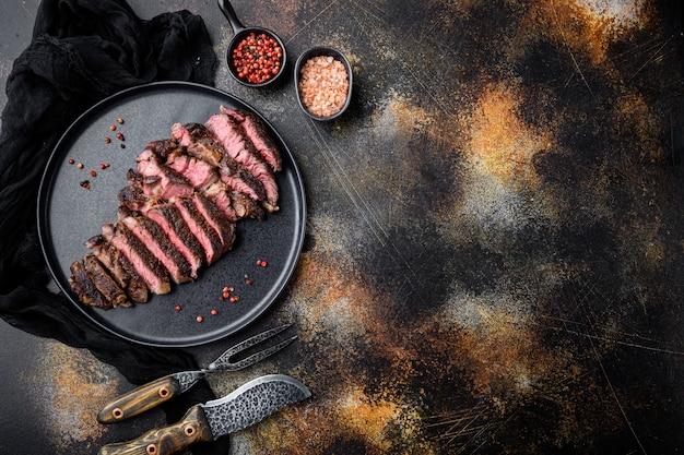 Conjunto de fatias de bife de rib eye suculento de carne média, no prato, com garfo e faca de carne, na velha mesa rústica escura, vista de cima plana lay