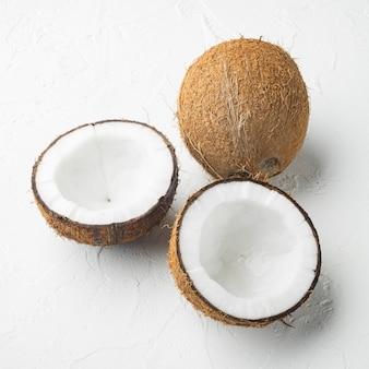 Conjunto de fatias de coco, no fundo da mesa de pedra branca, formato quadrado
