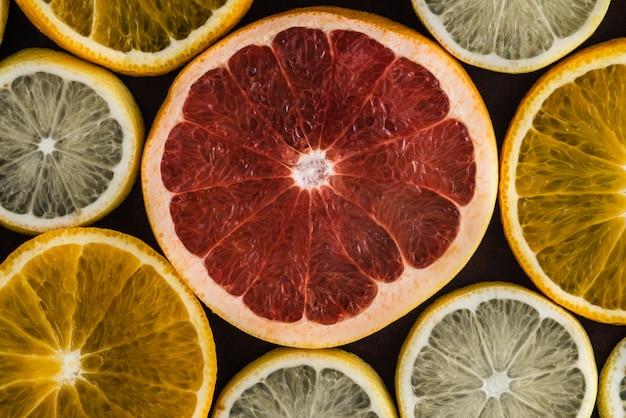 Conjunto de fatias de frutas cítricas em fundo escuro: laranja, limão, toranja.