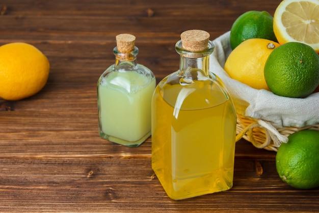 Conjunto de fatias de limão e cesta com recheio de limão e suco de limão em uma cesta sobre uma superfície de madeira. vista de alto ângulo.