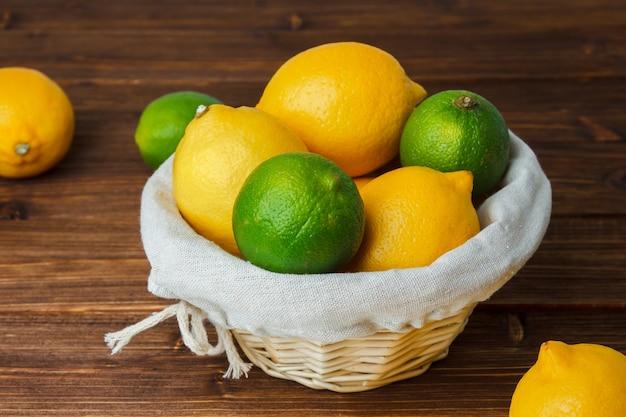 Conjunto de fatias de limão e limões amarelos e verdes em uma cesta sobre uma superfície de madeira. vista de alto ângulo.