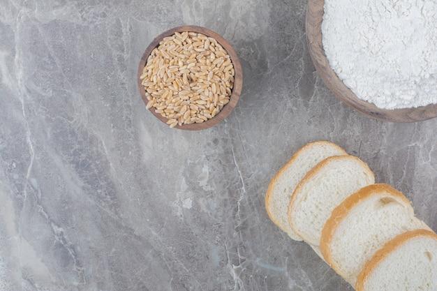 Conjunto de fatias de pão torrado com grãos de aveia na superfície de mármore