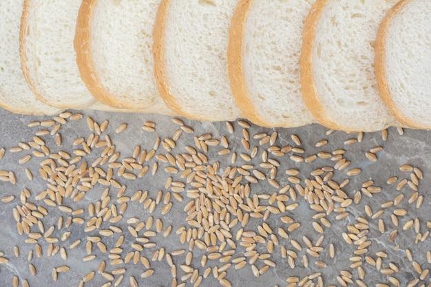 Conjunto de fatias de pão torrado com grãos de aveia no fundo de mármore.