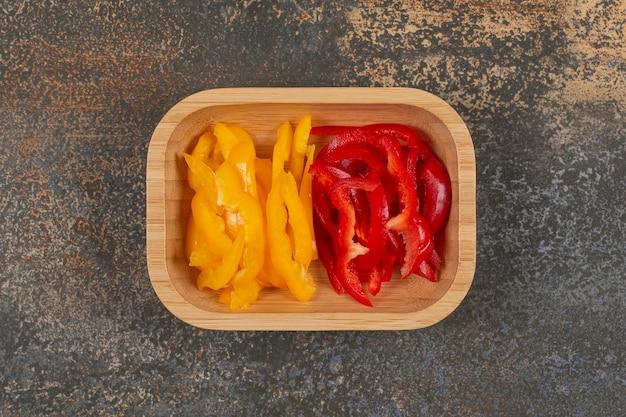 Conjunto de fatias de pimentão vermelho e amarelo na placa de madeira.