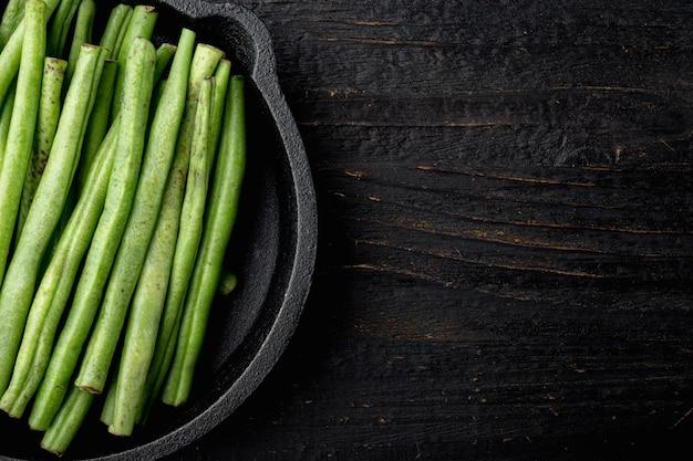 Conjunto de feijão verde fresco, em frigideira de ferro fundido, na mesa de madeira preta