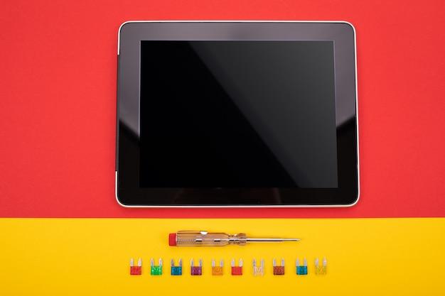 Conjunto de ferramenta elétrica e tablet preto na camiseta colorida