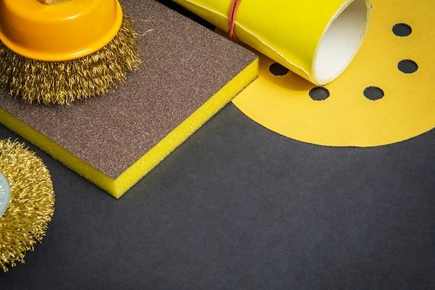 Conjunto de ferramentas abrasivas e lixa amarela no espaço preto