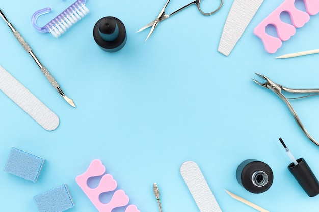 Conjunto de ferramentas cosméticas para manicure e pedicure em fundo azul. modelo de composição criativa para salão de beleza com lugar para texto
