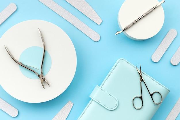 Conjunto de ferramentas cosméticas para manicure e pedicure em fundo azul. modelo de composição criativa para salão de beleza