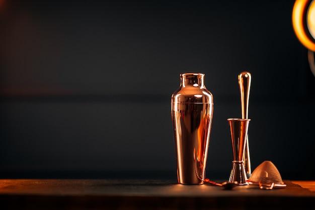 Conjunto de ferramentas de barra de cobre com agitador na mesa de madeira