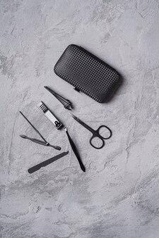 Conjunto de ferramentas de manicure, pedicure e acessórios com estojo, fundo de pedra de concreto, vista superior
