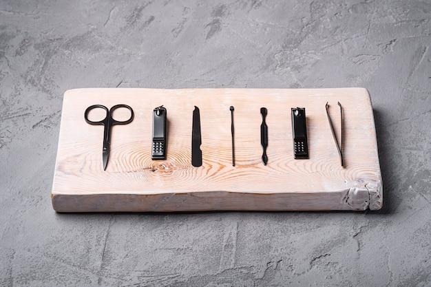 Conjunto de ferramentas de manicure, pedicure e acessórios na placa de madeira, fundo de pedra e concreto, vista angular