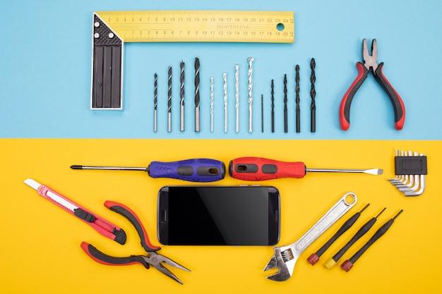 Conjunto de ferramentas de metalurgia com smartphone colorido
