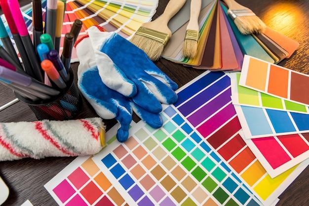 Conjunto de ferramentas de pintura como guia de paleta de papel colorido, luvas azuis e pincel na placa de madeira. conceito de construção e renovação