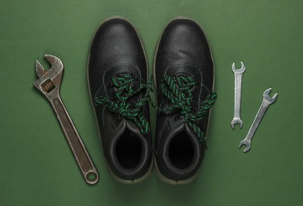 Conjunto de ferramentas de trabalho profissional e botas sobre fundo verde. vista do topo.