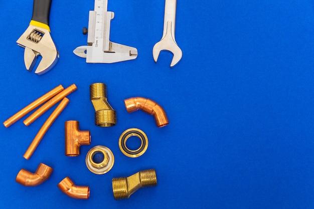 Conjunto de ferramentas e peças de reposição para encanamento isoladas no espaço azul, com espaço para publicidade