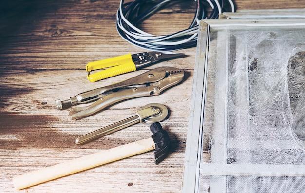 Conjunto de ferramentas manuais e tela de mosquito danificada que precisa ser consertada