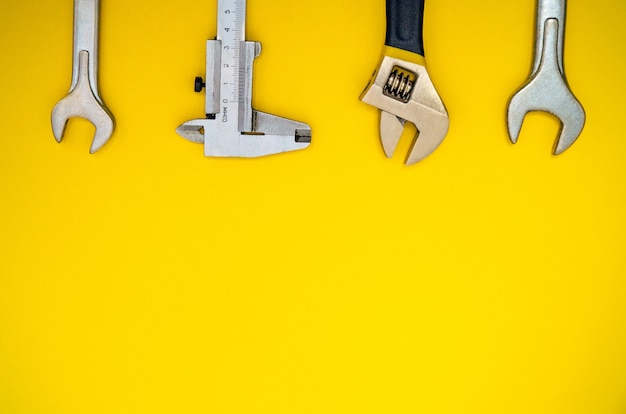 Conjunto de ferramentas para encanadores em fundo amarelo com espaço de cópia