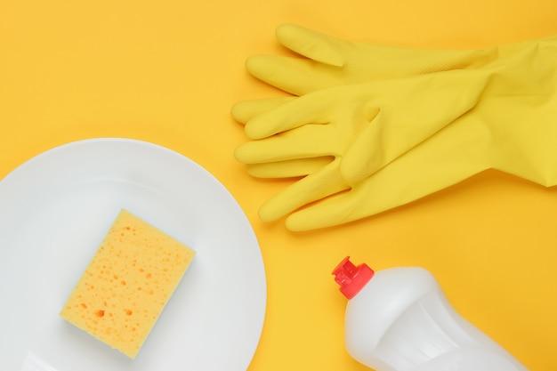 Conjunto de ferramentas para lavar pratos em fundo amarelo studio. prato, luvas de borracha, esponja, garrafa. vista do topo