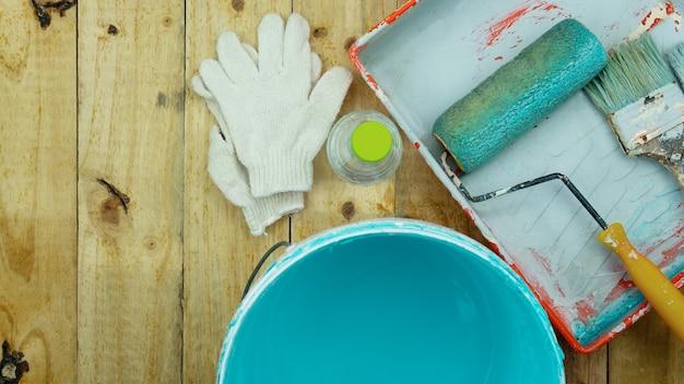 Conjunto de ferramentas para pintar parede com fundo de madeira em casa.