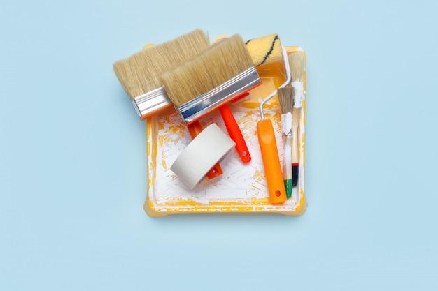 Conjunto de ferramentas para pintura: pincéis, fita adesiva, rolo de pintura sobre fundo azul claro.